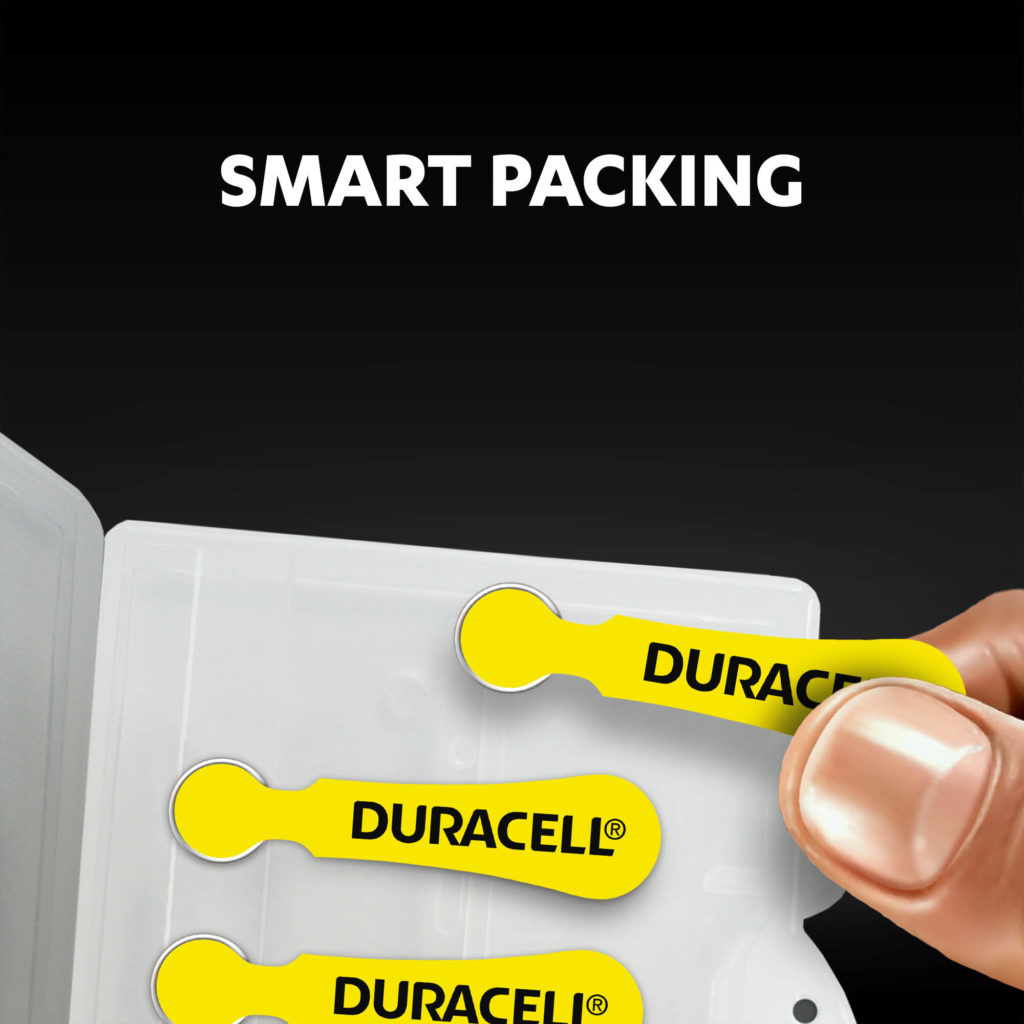 Fingers holding the hearing aids batteries from a package